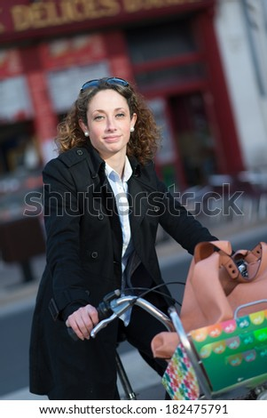 beautiful young woman riding bicycle in town - stock photo