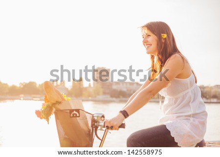Beautiful young woman riding bicycle with flowers in basket and enjoying spring time. - stock photo