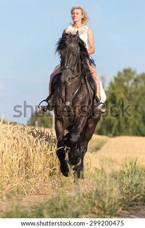 Beautiful young woman riding black stallion. - stock photo