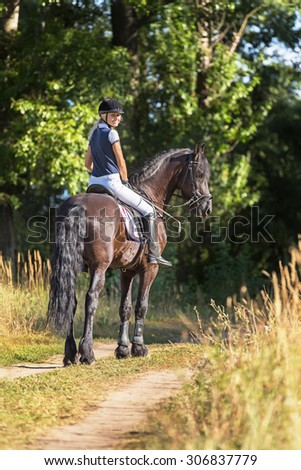 Beautiful young woman riding horse in a park.