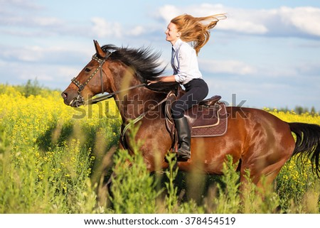 Beautiful young woman riding horse in meadow among yellow flowers.