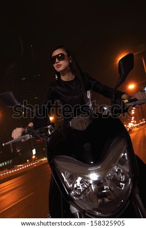 Beautiful young woman riding motorcycle in sunglasses at night