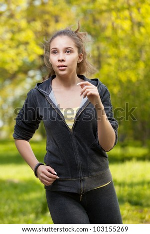 Beautiful young woman runner in a green forest. - stock photo