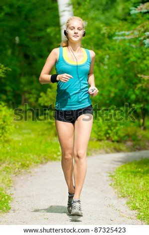 Beautiful young woman running in green park with music player - stock photo