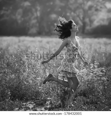 Beautiful young woman running in purple flowers outdoors - stock photo