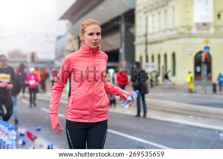 Beautiful young woman running in the city competition drinking water at the refreshment point