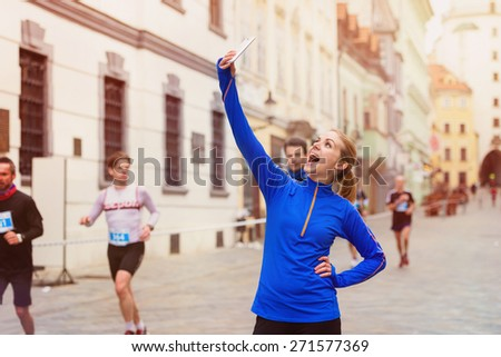 Beautiful young woman running in the city competition taking a selfie - stock photo