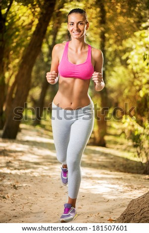 Beautiful young woman running in the nature.