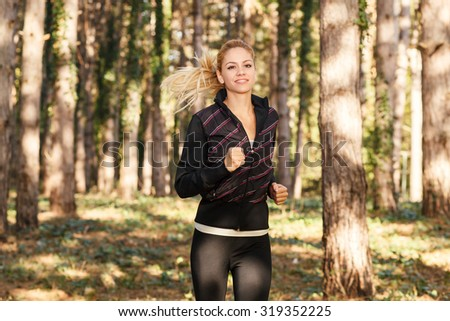 Beautiful young woman running through the park - stock photo