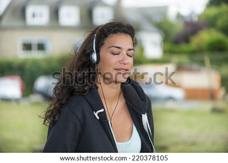 Beautiful young woman (20s) into dreams smiling with eyes closed. She is listening her favorite music in park. Silver headphones on ears. - stock photo