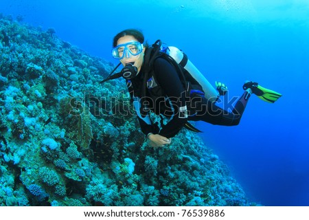Beautiful young woman scuba diving on a coral reef in the Sea - stock photo