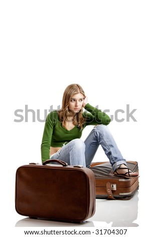 Beautiful young woman seated amd waiting with two old leather suitcases