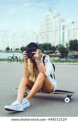 Beautiful young woman seating on skate and make self photo, street fashion lifestyle. outdoor portrait, posing in the street on hat, sneakers,  - stock photo