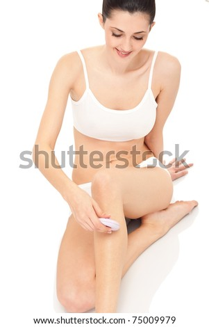 beautiful young woman shaving her legs with shaver,  body care, isolated on background - stock photo