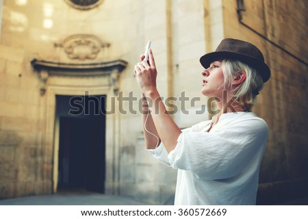 Beautiful young woman shoots video via mobile phone camera during excursion near vintage building outside,stylish female tourist making photo of architectural monument during while touring in the city - stock photo