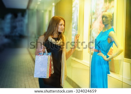 Beautiful young woman shopping at an outdoor mall - stock photo
