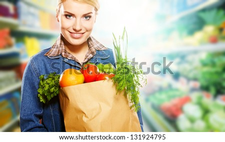 Beautiful young woman shopping for diary products at a grocery store/supermarket - stock photo