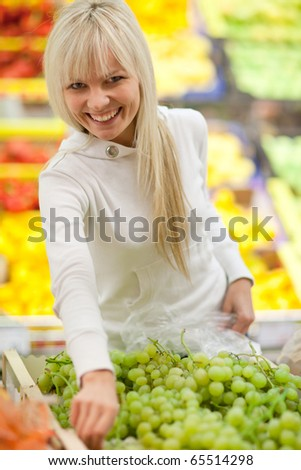 Beautiful young woman shopping for fruits and vegetables in produce department of a grocery store/supermarket (color toned image; shallow DOF) - stock photo