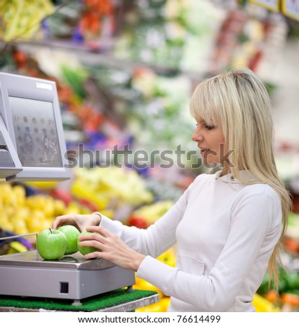 Beautiful young woman shopping for fruits and vegetables in produce department of a grocery store/supermarket (shallow DOF)