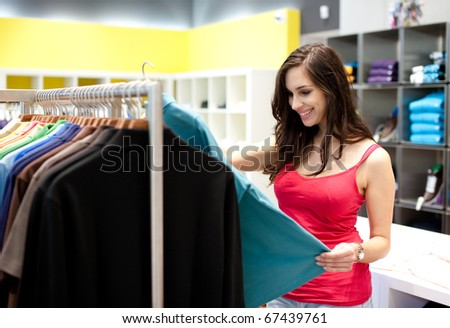 Beautiful young woman shopping in a department store. Shallow DOF. - stock photo