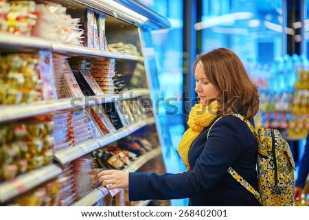 Beautiful young woman shopping in a grocery store/supermarket - stock photo
