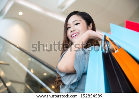 beautiful young woman shopping in mall, holding shopping bags standing on escalator
