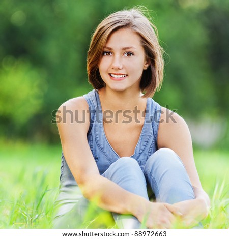 beautiful young woman short hair sitting alone grass meadow - stock photo