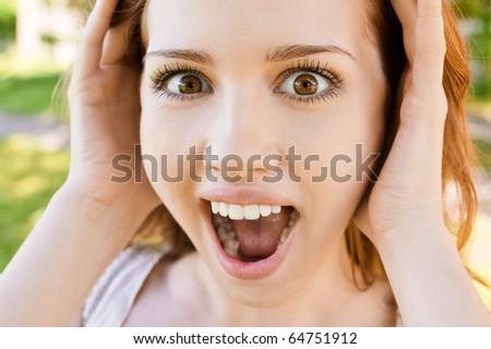 Beautiful young woman shouts loud voice, against green summer garden. - stock photo