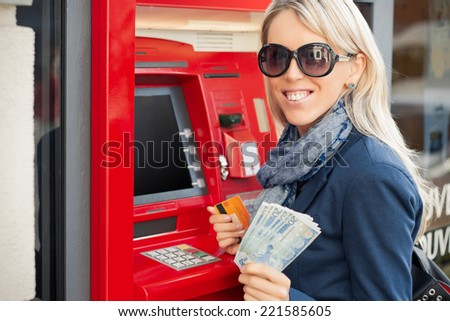 Beautiful young woman showing cash after withdrawal from ATM - stock photo