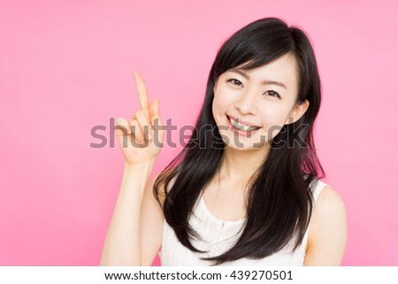 beautiful young woman showing copy space against pink background