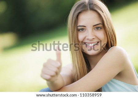 Beautiful young woman showing thumb up sign