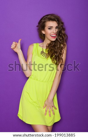 Beautiful young woman showing thumb up. Three quarter length studio shot on violet background. - stock photo