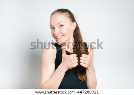 beautiful young woman showing thumbs up, isolated on a gray background - stock photo