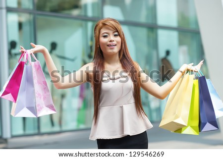 Beautiful young woman shows an ecstatic expression while holding shopping bags outside shopping mall. - stock photo