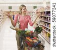 Beautiful young woman shrugs her shoulders while shopping in a grocery store.  Square shot. - stock photo