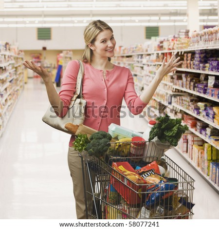 Beautiful young woman shrugs her shoulders while shopping in a grocery store.  Square shot.