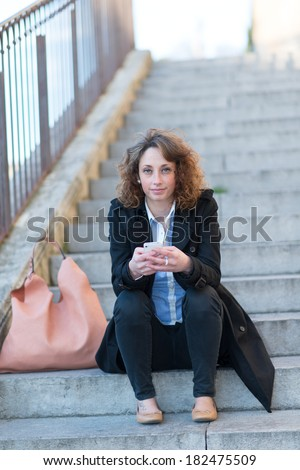 beautiful young woman siting in a staircase outdoor - stock photo