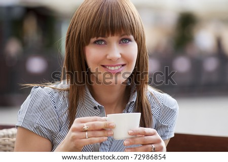 beautiful young woman sitting alone in a cafe outdoor and drinking a cup of tea looking in camera - stock photo