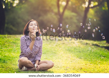 beautiful young woman sitting and  blowing bubble in the park - stock photo