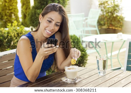 Beautiful young  woman  sitting at a desk in cafe and reading a message on her smart phone.  - stock photo