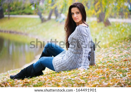 Beautiful young woman sitting at autumn park - stock photo