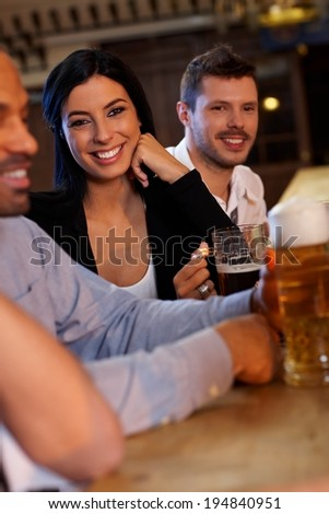 Beautiful young woman sitting at pub with friends, drinking beer. Looking at camera, smiling. - stock photo
