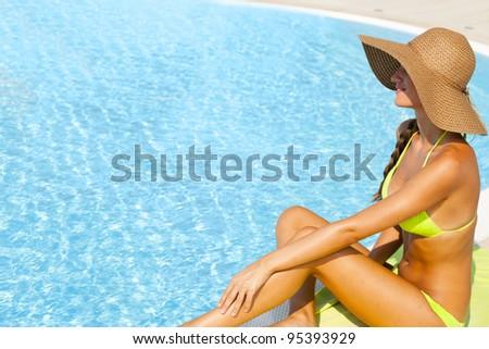 Beautiful young woman sitting by swimming-pool - stock photo