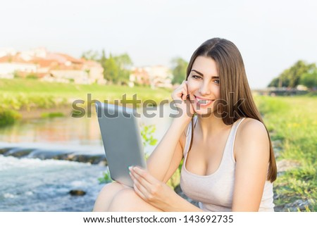 Beautiful young woman sitting by the river using tablet computer - stock photo