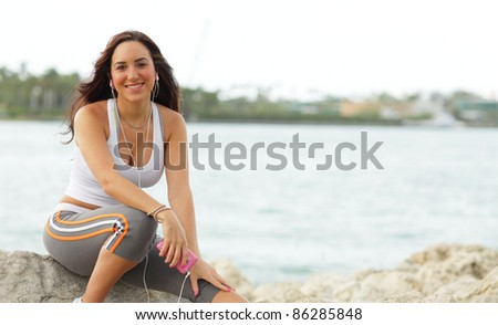Beautiful young woman sitting by the water - stock photo