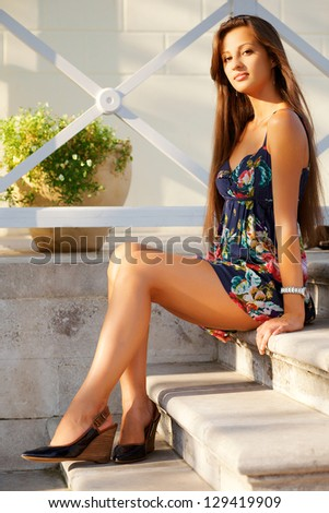 Beautiful young woman sitting elegantly on ��° stairs - stock photo