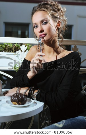 beautiful young woman sitting in a cafe eating cake and drink coffee - stock photo