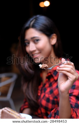 beautiful young woman sitting in a cafe eating cake.(focus on cake) - stock photo