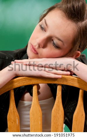 Beautiful young woman sitting in a chair - stock photo