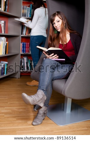 Beautiful young woman sitting in a lounge chair in the library reading a book - stock photo